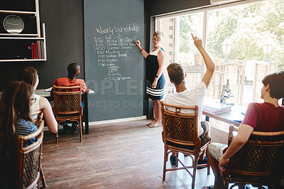 Buy stock photo Cropped shot of a group of focused young students seated at desks while the teacher gives class