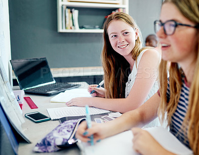 Buy stock photo Cropped shot of two young students doing schoolwork together while being seated at their desks