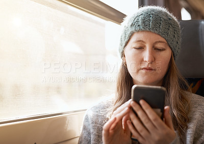 Buy stock photo Cropped shot of an attractive young woman sending text messages while sitting on a train