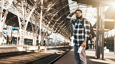 Buy stock photo Cropped shot of a handsome young man waiting for a train at the station