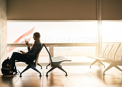 Buy stock photo Shot of a young woman using her cellphone while sitting in the airport lounge area