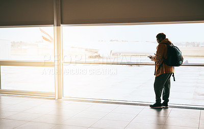Buy stock photo Shot of a young man using his cellphone while waiting at the airport