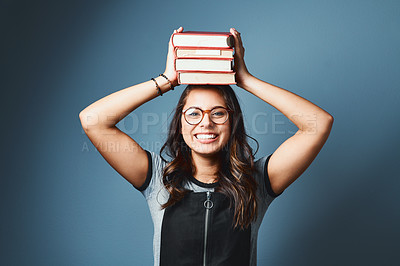 Buy stock photo Studio portrait of an attractive young woman balancing a pile of books on her head against a blue background
