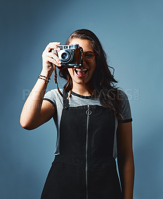 Buy stock photo Studio portrait of an attractive young woman taking photos with a vintage camera against a blue background