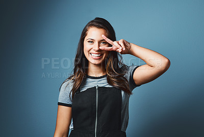 Buy stock photo Studio portrait of an attractive young woman showing the peace sign against a blue background