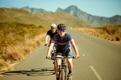 Buy stock photo Shot of a man and woman riding their bicycles in the countryside