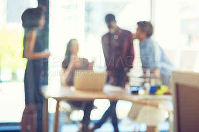 Buy stock photo Defocused shot of a group of businesspeople working together in an office