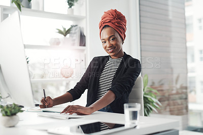 Buy stock photo Cropped portrait of an attractive young businesswoman taking notes while working at her desk in the office