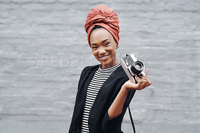 Buy stock photo Cropped portrait of an attractive young businesswoman posing with her camera against a grey brick wall outside
