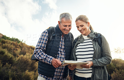 Buy stock photo Shot of a mature couple using a map while hiking through the mountains