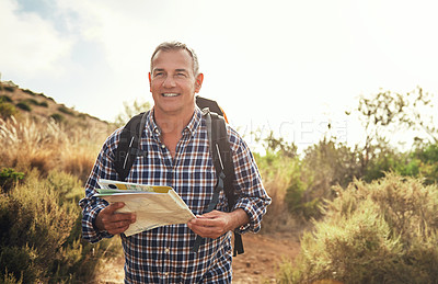 Buy stock photo Shot of a mature man using a map while hiking through the mountains