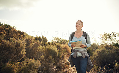 Buy stock photo Shot of a mature woman using a map while hiking through the mountains