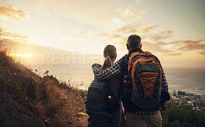 Buy stock photo Rearview shot of a mature couple looking at the view hiking through the mountains