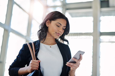 Buy stock photo Cropped shot of an attractive young businesswoman using her smartphone in her office