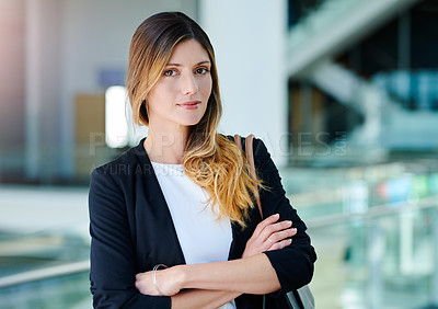 Buy stock photo Cropped portrait of an attractive young businesswoman standing with her arms crossed in an office