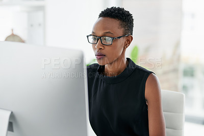 Buy stock photo Shot of a confident young businesswoman using a computer in a modern office