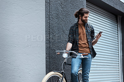 Buy stock photo Shot of a handsome young man travelling with his bicycle outdoors