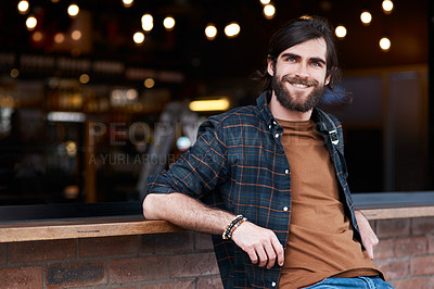 Buy stock photo Portrait of a handsome young man posing outside a cafe in the city