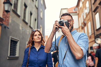 Buy stock photo Shot of a man taking pictures while out exploring a foreign city with his wife