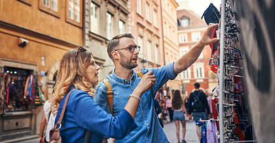 Buy stock photo Cropped shot of a couple trying on sunglasses while exploring a foreign city