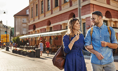 Buy stock photo Shot of a woman enjoying an ice cream while exploring a foreign city with her boyfriend