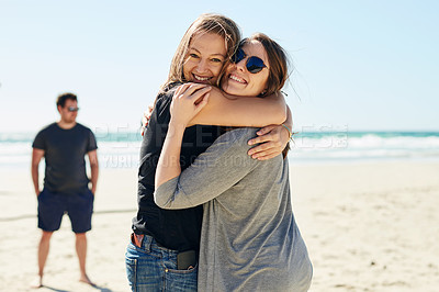 Buy stock photo Shot of two young women standing together while at the beach with friends