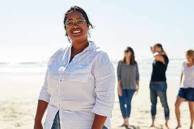 Buy stock photo Portrait of a young woman standing on the beach while her friends stand in the background