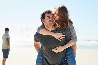 Buy stock photo Cropped shot of a man piggybacking his girlfriend on the beach
