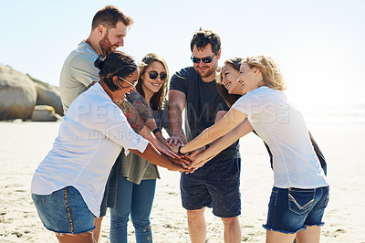 Buy stock photo Cropped shot of friends standing with their hands huddled on the beach