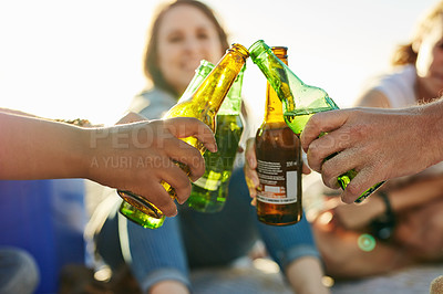 Buy stock photo Cropped shot of a group of friends toasting with drinks at the beach