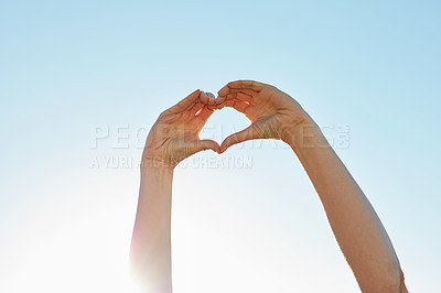 Buy stock photo Cropped shot of an unrecognizable woman forming a heart shape with her hands