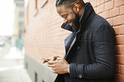 Buy stock photo Shot of a handsome and fashionable young man texting on his cellphone while being out in the city