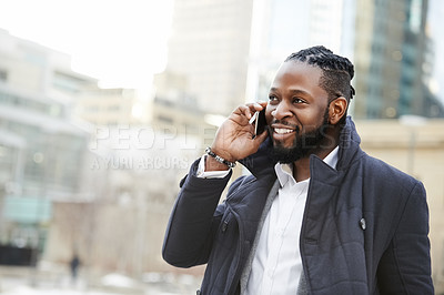 Buy stock photo Shot of a handsome and fashionable young man talking on his cellphone while being out in the city