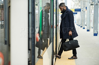 Buy stock photo Shot of a handsome and fashionable young man waiting for a train at a station outside in a busy city
