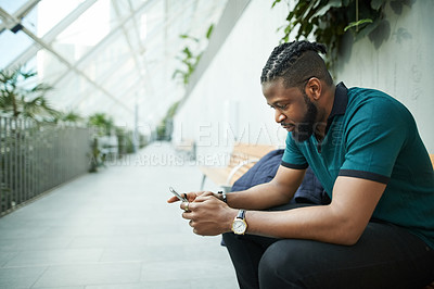 Buy stock photo Shot of a handsome young man using his cellphone while sitting on a bench outdoors