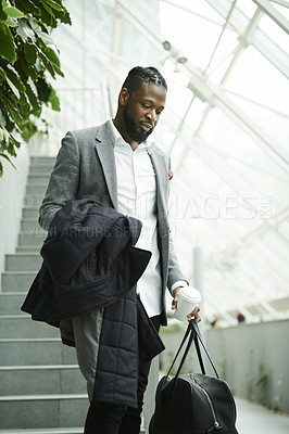 Buy stock photo Shot of a handsome young businessman heading down a flight of stairs