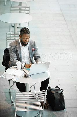 Buy stock photo Shot of a handsome young businessman working on his laptop while relaxing outdoors