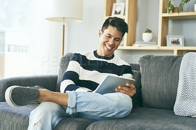 Buy stock photo Cropped shot of a happy young man using a digital tablet while relaxing on the sofa at home