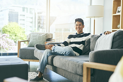 Buy stock photo Full length portrait of a happy young man relaxing on the sofa at home