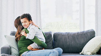 Buy stock photo Cropped shot of an adorable little boy embracing his mother in their living room