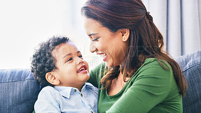 Buy stock photo Cropped shot of an attractive young woman and her son embracing in their living room