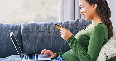 Buy stock photo Cropped shot of an attractive young woman shopping online using her laptop in the living room
