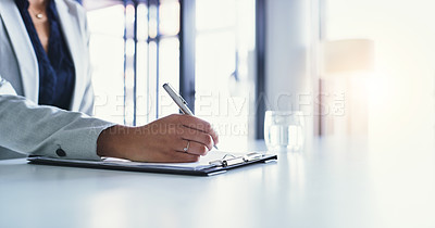 Buy stock photo Cropped shot of an unrecognizable businesswoman making notes on a clipboard inside of the office