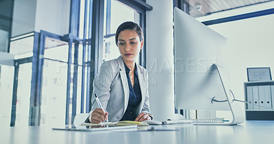 Buy stock photo Cropped shot of a focused young businesswoman working on a computer and making notes inside of the office