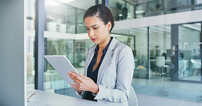 Buy stock photo Cropped shot of a focused young businesswoman browsing on a digital tablet inside of the office