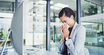 Buy stock photo Cropped shot of a carefree young businesswoman blowing her nose with a tissue inside of the office during the day