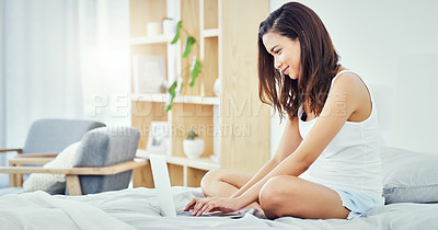 Buy stock photo Full length shot of an attractive young woman sitting on her bed and using her laptop at home