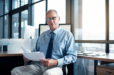 Buy stock photo Shot of a mature businessman working on paperwork in his office