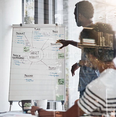 Buy stock photo Shot of a young designer giving a presentation to his colleagues in an office