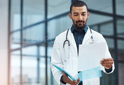 Buy stock photo Shot of a young doctor going over the contents of a file in a modern hospital